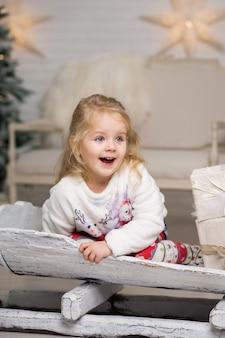 Meisje rodelen met kerstcadeau doos.
