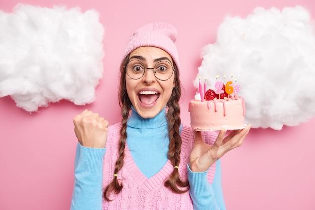 Meisje roept luid balt vuist van vreugde houdt heerlijke taart viert verjaardag draagt ronde bril roze hoed vrijetijdskleding geïsoleerd op rooskleurig