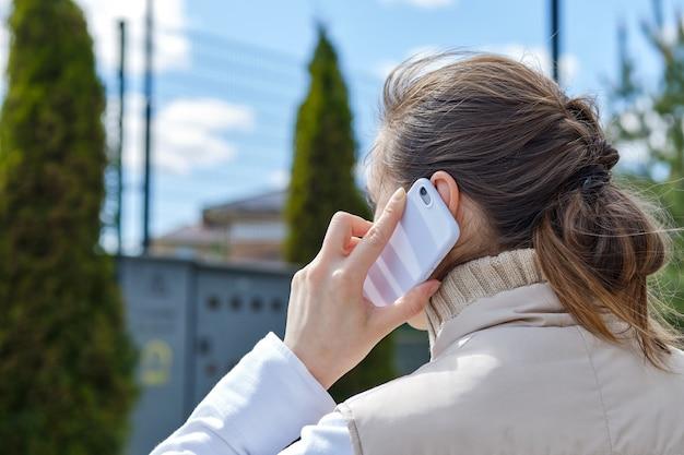Meisje roept via smartphone terwijl ze over straat loopt.