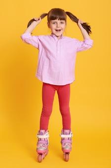 Meisje rolschaatsen tegen gele ruimte
