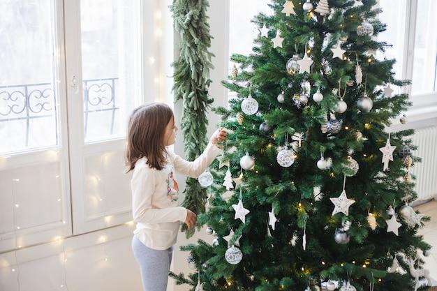 Meisje rond de kerstboom, wachtend op geschenken en vakantie, kersttradities, kerstmis en familie