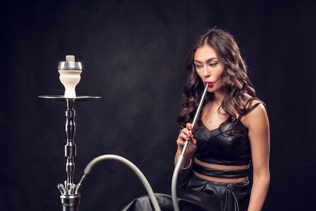 Meisje rookt waterpijp / mooi glamoureus meisje in zwarte jurk rookt een waterpijp