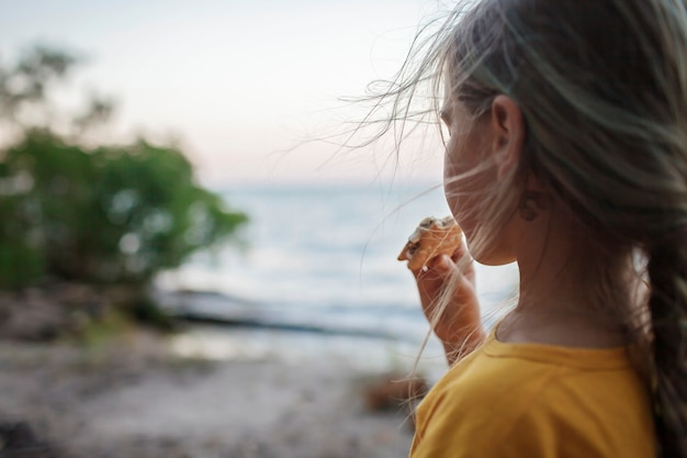 Meisje roostert marshmallow om smores te maken boven vuur tijdens het kamperen met traditioneel reisvoedsel