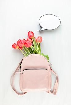 Meisje roze letherrugzak met rode tulpen en de lichte doos van de toespraakbel.