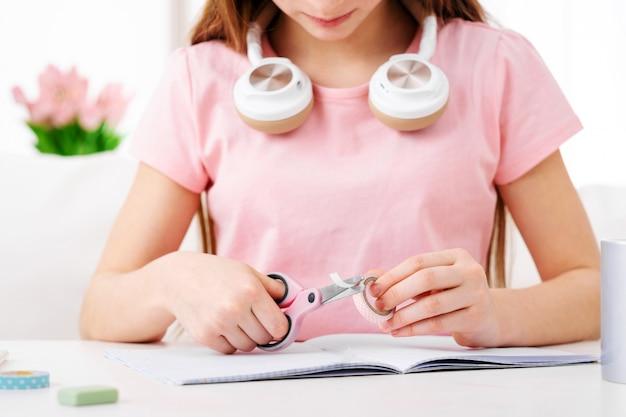 Meisje roze papier snijden