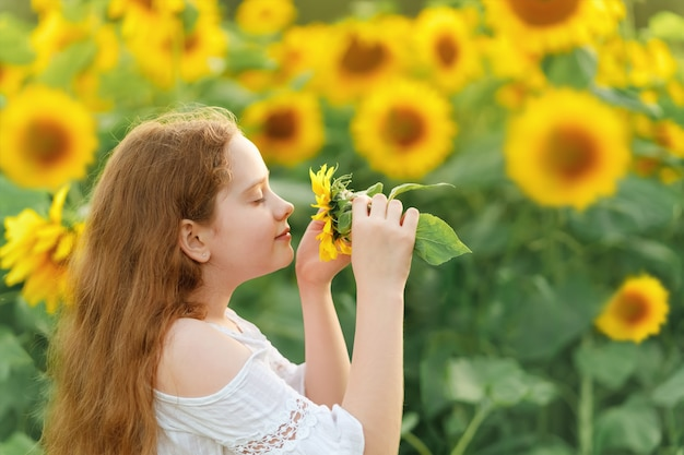 Meisje ruikende zonnebloem, genietend van de natuur buiten.