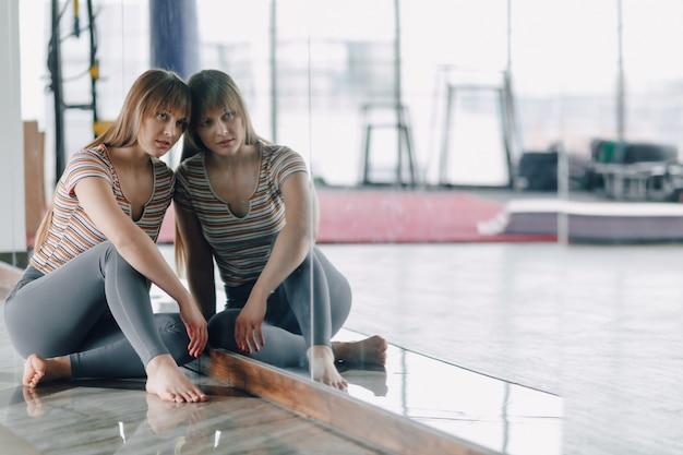 Meisje rusten op de vloer in de buurt van de spiegel