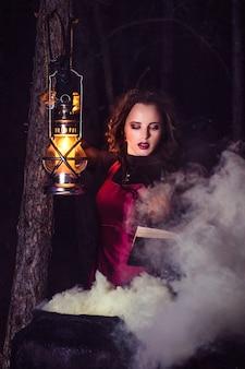 Meisje 's nachts alleen in het bos brouwt een drankje en vraagt zich af voor het huwelijk, omringd door kaarsen en rook