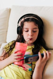 Meisje sap drinken en kijken naar telefoon