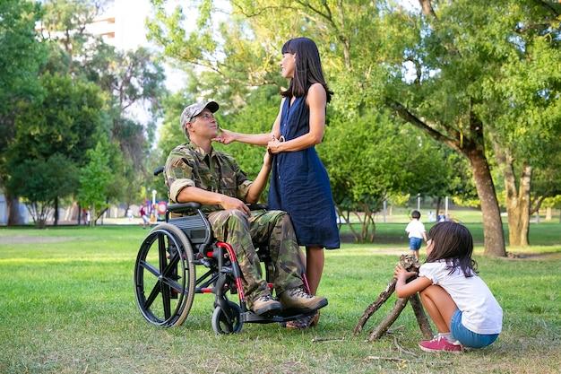 Meisje schikken brandhout voor kampvuur buitenshuis terwijl haar moeder en gehandicapte militaire vader hand in hand en praten. gehandicapte veteraan of familie buitenshuis concept