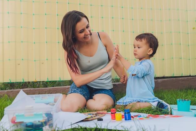 Meisje schilderij met haar moeder in de achtertuin