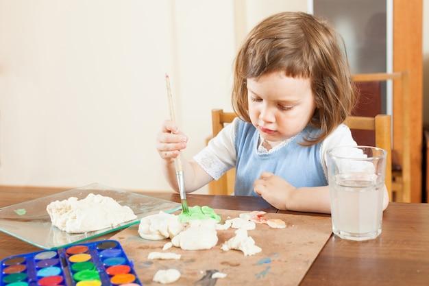 Meisje schildert deeg beeldjes