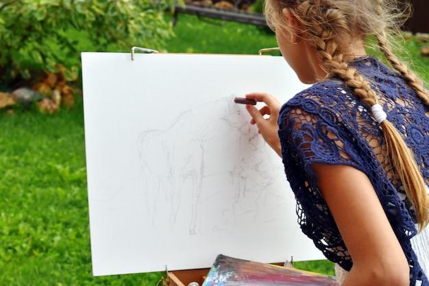 Meisje schildert een afbeelding op een schetsboek buiten