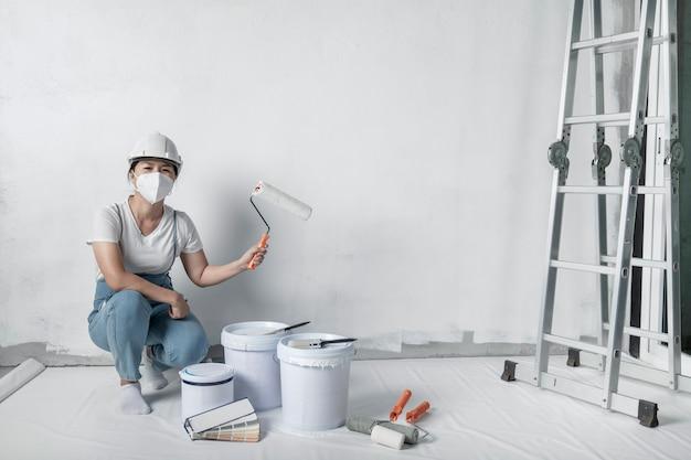Meisje schildert een witte muur met een roller. reparatie van het interieur.