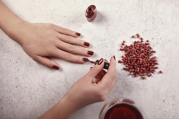 Meisje schildert haar nagels de gel polish. witte achtergrond, glas wijn, rode details. mooie hand. nagel verlenging. manicure, kuuroordsalon. creatief, reclame.