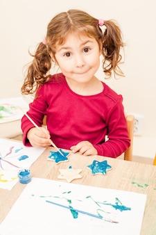 Meisje schildert met een penseel en aquarellen op kleifiguren