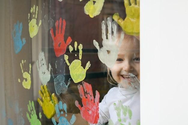 Meisje schildert met handpalmen op het raam. quarantaine blijf thuis