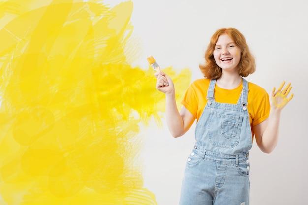 Meisje schildert witte muur in geel