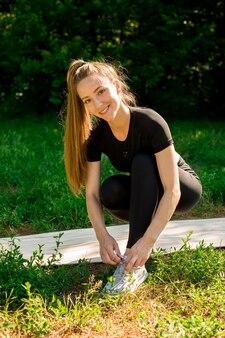 Meisje schoenveters binden voor training. ze trainde in de natuur.