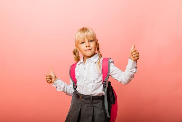 Meisje schoolmeisje toont gebaar van goedkeuring van de klas met beide handen geïsoleerd op roze achtergrond.
