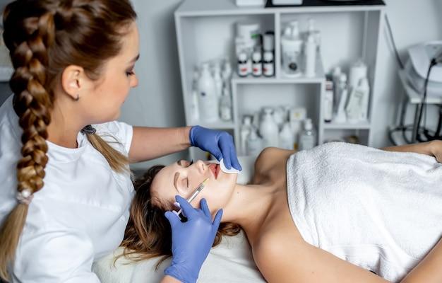 Meisje schoonheidsspecialiste maakt injecties op de lippen en het gezicht van een mooie vrouw in een cosmetische wig. cosmetologie concept.