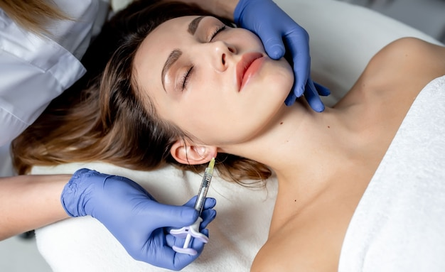 Meisje schoonheidsspecialiste maakt injecties op de lippen en het gezicht van een mooie vrouw in een cosmetische wig