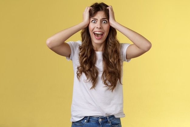 Meisje schreeuwende paniek. verontruste verontruste angstige vrouw zie enorme puinhoop doodsbang voel verdriet schreeuwen geschokt pak hoofd hopeloos probleem vreselijke situatie schreeuwen schudde verbijsterde gele achtergrond.