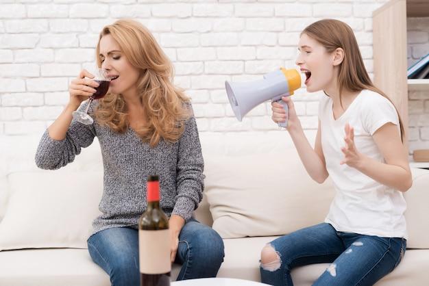 Meisje schreeuwt in een megafoon tegen moeder die drinkt.