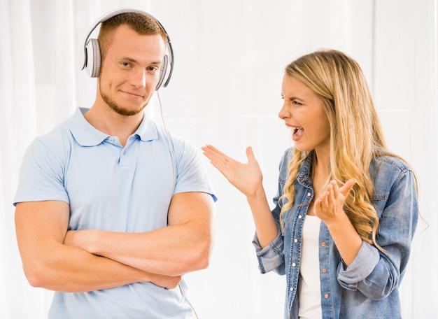 Meisje schreeuwt tegen een man die in de koptelefoon staat.