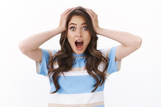 Meisje schreeuwt verbaasd en blij, hoofd geneest van uitstekend geweldig nieuws, open mond geschokt, schreeuwend onder de indruk, staren naar camera verbazing grijp het hoofd