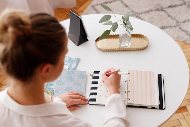 Meisje schrijft in een notitieblok op kantoor. bovenaanzicht van de werkplek
