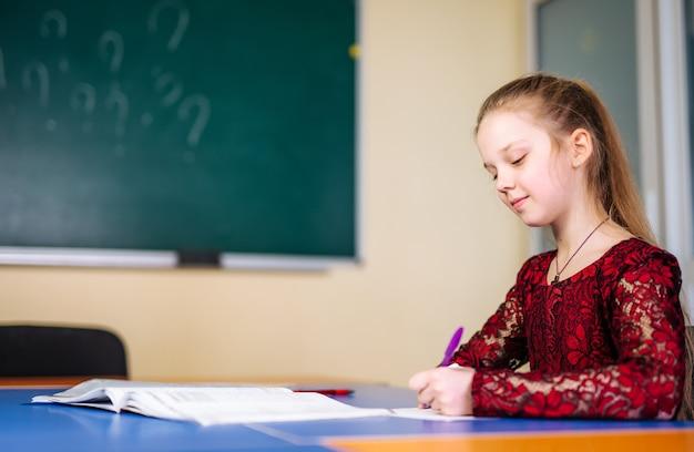 Meisje schrijven les in leerboek. netjes en schattig meisje op school. onderwijsconcept. terug naar school.