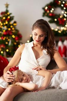 Meisje slaapt op moeders schoot