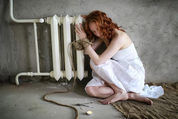 Meisje slachtoffer van ontvoering zit vastgebonden op de grond in wit overhemd