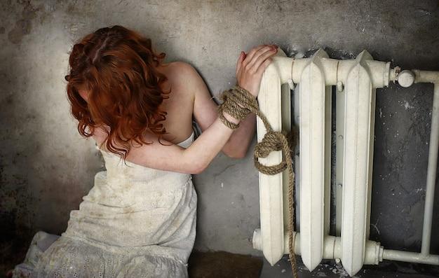 Meisje slachtoffer van ontvoering zit vastgebonden op de vloer in een verlaten gebouw