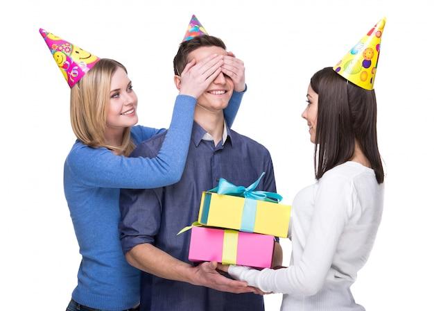 Meisje sluit haar ogen voor de man en de andere houdt een geschenk vast.