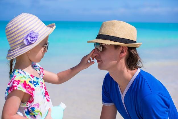 Meisje smeert de neus van haar vader zonbeschermingscrème