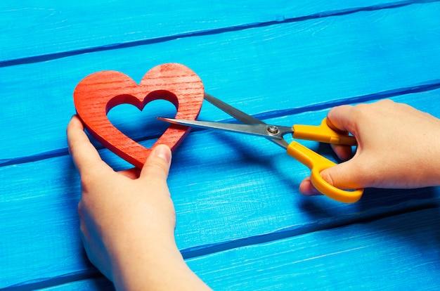 Meisje snijdt het hart met een schaar, het concept van het verbreken van relaties, ruzies en echtscheiding.