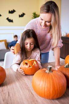 Meisje snijdt pompoen voor halloween