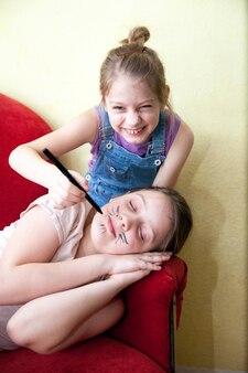 Meisje snor puttend uit gezicht van haar slapende zus. april fool's day