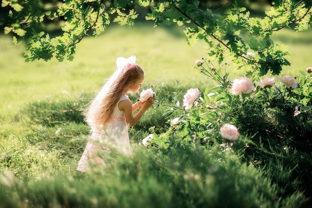 Meisje snuift bloemen. een kind zorgt in de zomer voor pioenrozen