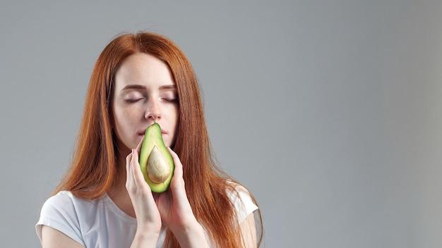Meisje snuiven avocado. jonge roodharige meisje toont avocado naar de camera