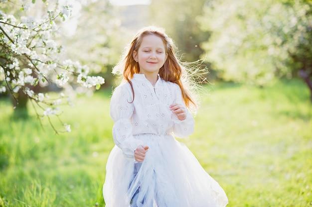 Meisje snuiven bloemen van appelboomgaard. tuin met bloeiende bomen