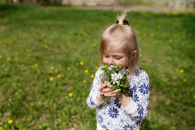 Meisje snuiven lentebloemen op groen gazon in de tuin.