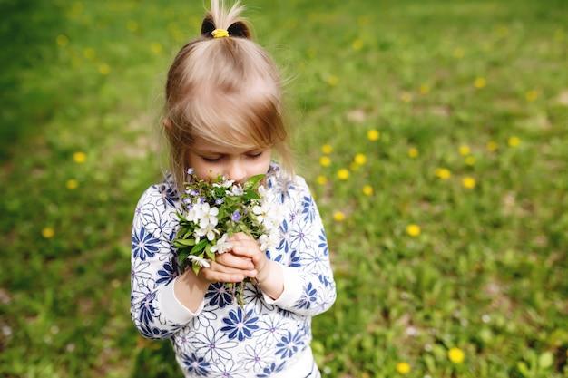 Meisje snuiven lentebloemen op groen gazon in de tuin