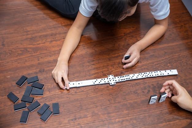 Meisje speelt domino in het huis