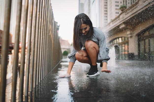 Meisje speelt en danst rond in een natte straat