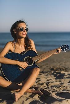 Meisje speelt gitaar op het strand