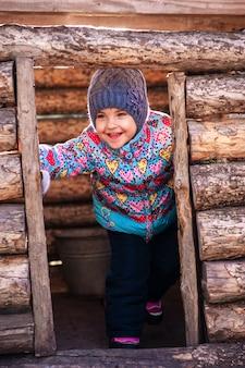 Meisje speelt in een houten huis