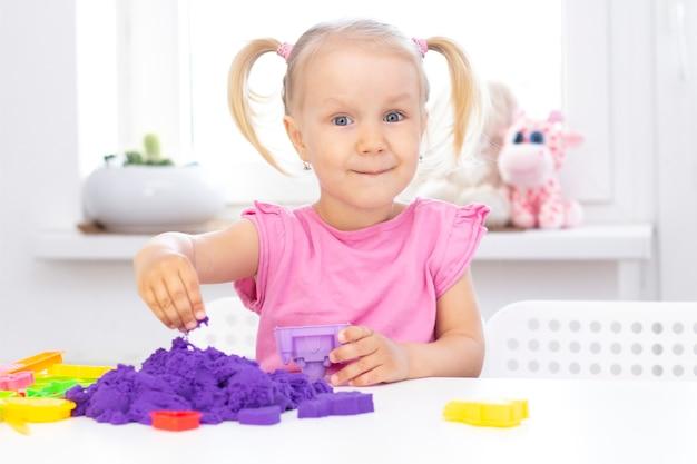 Meisje speelt kinetisch zand in quarantaine. blond mooi meisje glimlacht en speelt met paars zand op een witte tafel.